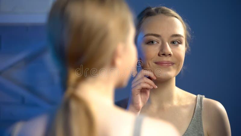 Όμορφο κορίτσι σχετικά με το του προσώπου δέρμα κοντά στον καθρέφτη, που ικανοποιεί με την αντανάκλαση, ομορφιά στοκ εικόνα