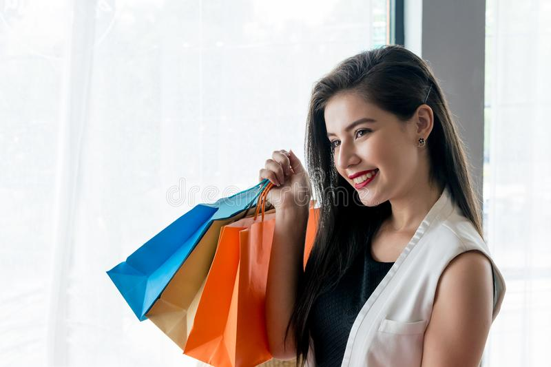 Όμορφο κορίτσι χαμόγελου που κρατά τη ζωηρόχρωμη τσάντα αγορών στοκ εικόνες με δικαίωμα ελεύθερης χρήσης