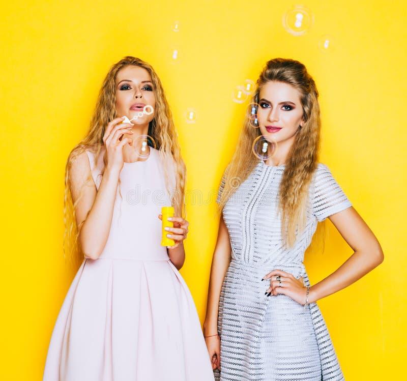 Όμορφο κορίτσι δύο το εύθυμο φίλων διογκώνει τις φυσαλίδες σαπουνιών και κατοχή της διασκέδασης στοκ εικόνα με δικαίωμα ελεύθερης χρήσης