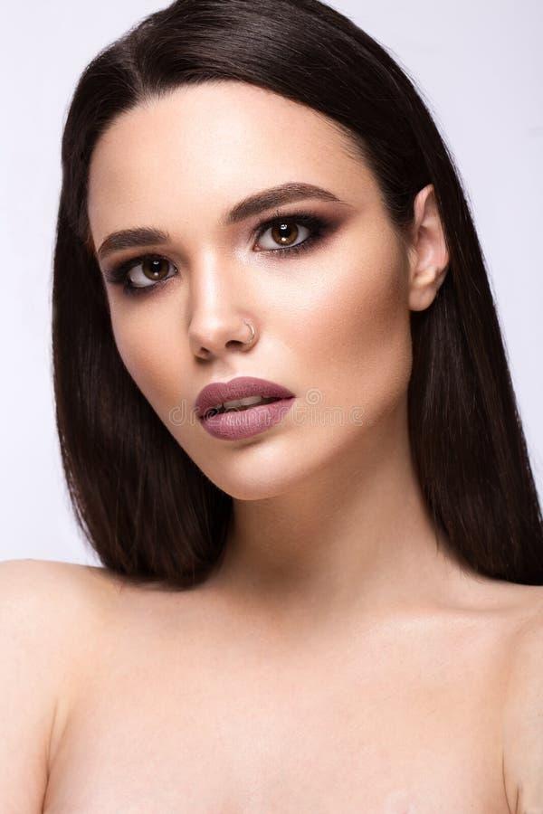 Όμορφο κορίτσι brunette με μια τέλεια ομαλή τρίχα και μια κλασική σύνθεση Πρόσωπο ομορφιάς στοκ εικόνες