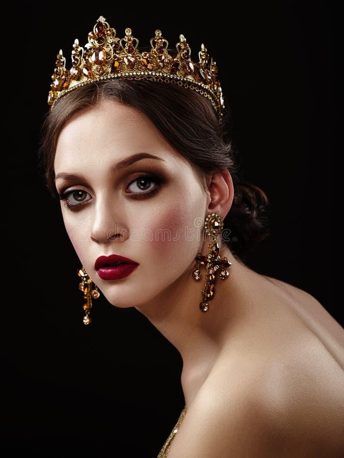Όμορφο κορίτσι brunette με μια χρυσή κορώνα, σκουλαρίκια και profes στοκ εικόνες