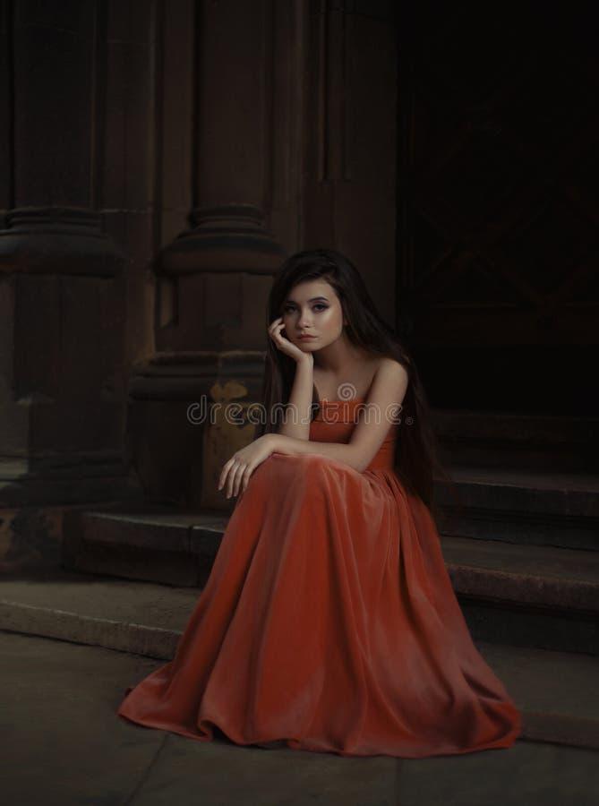 Όμορφο κορίτσι brunette, με πολύ μακρυμάλλη, σε ένα πορτοκαλί, εκλεκτής ποιότητας φόρεμα στοκ εικόνες