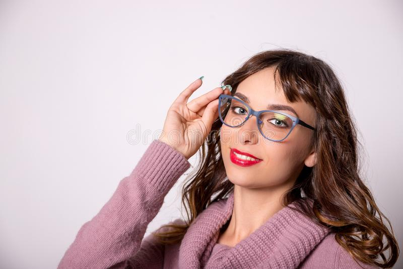 Όμορφο κορίτσι brunette με τα κόκκινα χείλια και τη φθορά των γυαλιών με ένα μπλε πλαίσιο που χαμογελά σε ένα άσπρο υπόβαθρο _ στοκ εικόνες με δικαίωμα ελεύθερης χρήσης