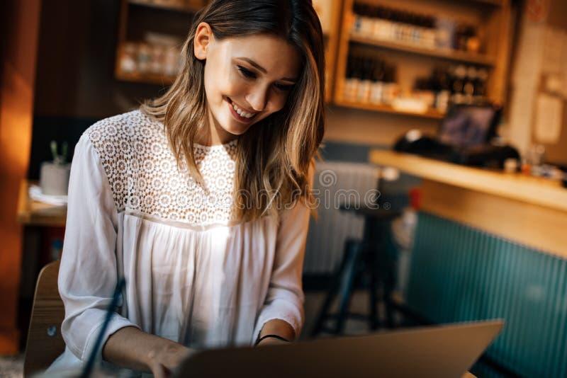 Όμορφο κορίτσι brunette που χρησιμοποιεί το lap-top για την εργασία, ανεξάρτητος, μελέτη, αγορές στοκ εικόνα