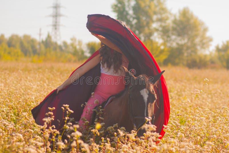 όμορφο κορίτσι, brunette σε ένα κόκκινο αδιάβροχο στοκ φωτογραφίες