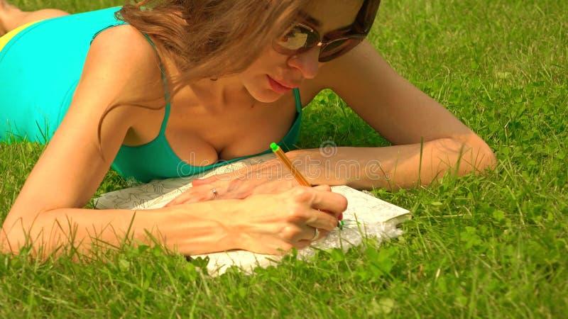 Όμορφο κορίτσι brunette στα γυαλιά ηλίου που βάζει στη χλόη και στοκ φωτογραφία με δικαίωμα ελεύθερης χρήσης