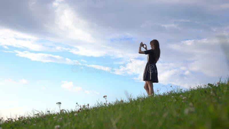 Όμορφο κορίτσι brunette στο μαύρο φόρεμα που στέκεται στο χλοώδη λόφο και που κάνει τις φωτογραφίες με το τηλέφωνό της Ερασιτεχνι στοκ εικόνες