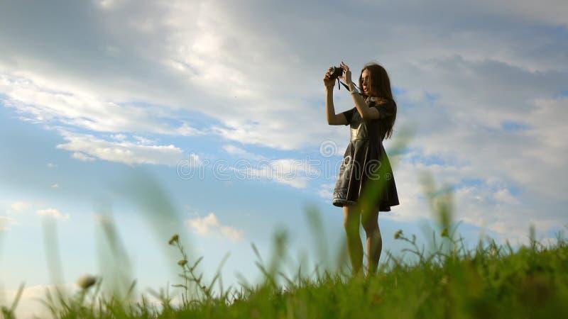 Όμορφο κορίτσι brunette στο μαύρο φόρεμα που στέκεται στο λόφο και που κάνει τις φωτογραφίες με τη συμπαγή κάμερα της _ στοκ φωτογραφίες