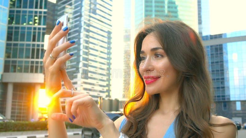 Όμορφο κορίτσι brunette στο μπλε φόρεμα που κάνει selfie στο ηλιοβασίλεμα ενάντια στους ουρανοξύστες στοκ φωτογραφία