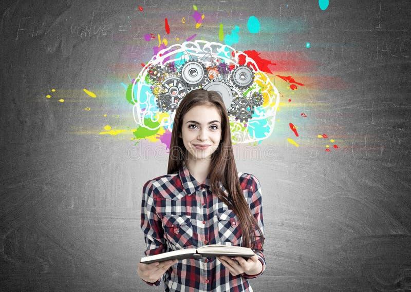 Όμορφο κορίτσι geek με τα βαραίνω βιβλίων και εγκεφάλου στοκ φωτογραφία με δικαίωμα ελεύθερης χρήσης