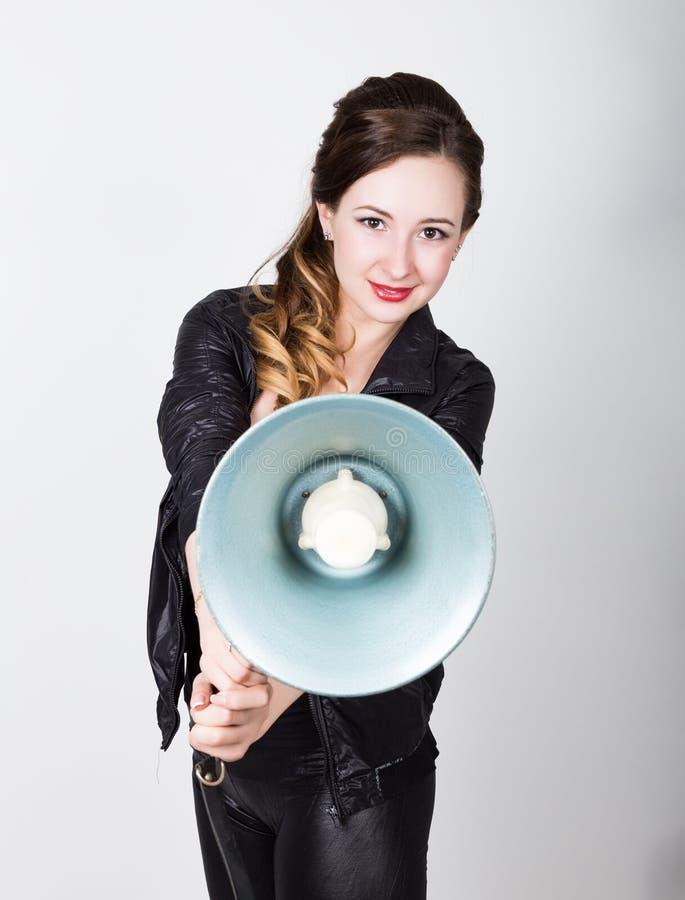Όμορφο κορίτσι Leggy στο μαύρα εφαρμοστά παντελόνι και το σακάκι, φωνάζει σε ένα bullhorn Δημόσιες σχέσεις στοκ εικόνα με δικαίωμα ελεύθερης χρήσης