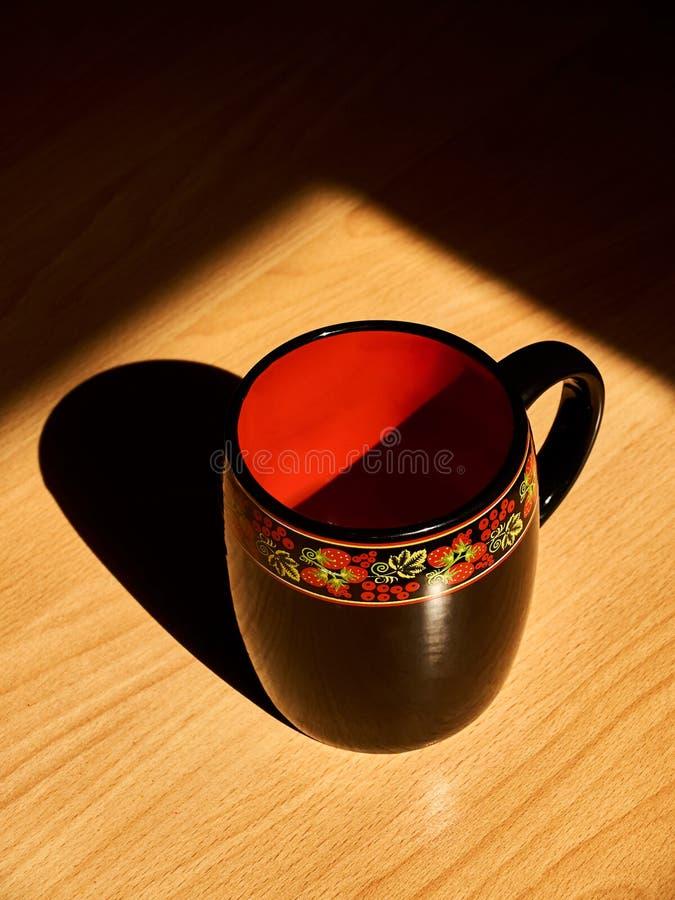 Όμορφο κόκκινο και μαύρο φλυτζάνι με την παραδοσιακή ρωσική ζωγραφική στοκ φωτογραφία