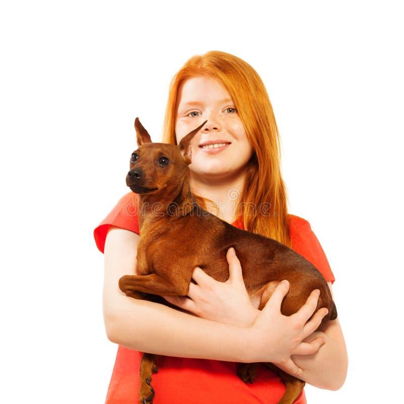 Όμορφο κόκκινο χαμογελώντας κορίτσι με το σκυλί σε ετοιμότητα της στοκ φωτογραφία με δικαίωμα ελεύθερης χρήσης