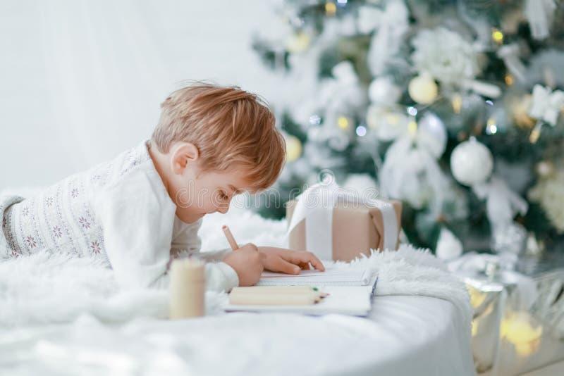 Όμορφο λίγο αγοράκι στις πυτζάμες με τα αστέρια γιορτάζει τα Χριστούγεννα Νέες διακοπές έτους ` s Παιχνίδι μικρών παιδιών στο λευ στοκ εικόνα
