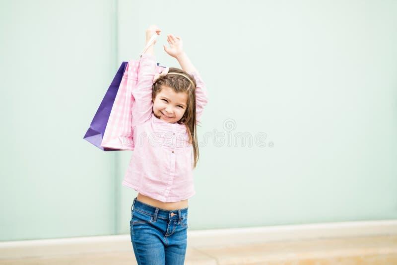 Όμορφο λίγο λατινικό κορίτσι με τις αγορές τοποθετεί σε σάκκο υπαίθρια στοκ εικόνα