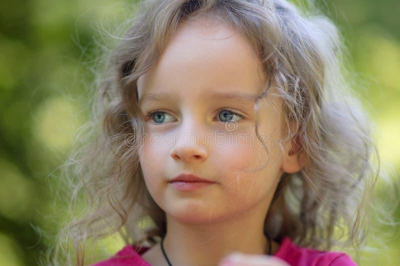 Όμορφο λίγο σγουρό ξανθό κορίτσι, έχει τη σοβαρή έκφραση, εξετάζει την απόσταση, μεγάλα μπλε μάτια, μακροχρόνια eyelashes στοκ εικόνες