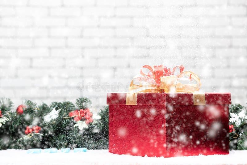 Όμορφο λαμπρό κιβώτιο δώρων που έχει το χιόνι που αφορά το, καθορισμένος σε χιονώδη στοκ εικόνες