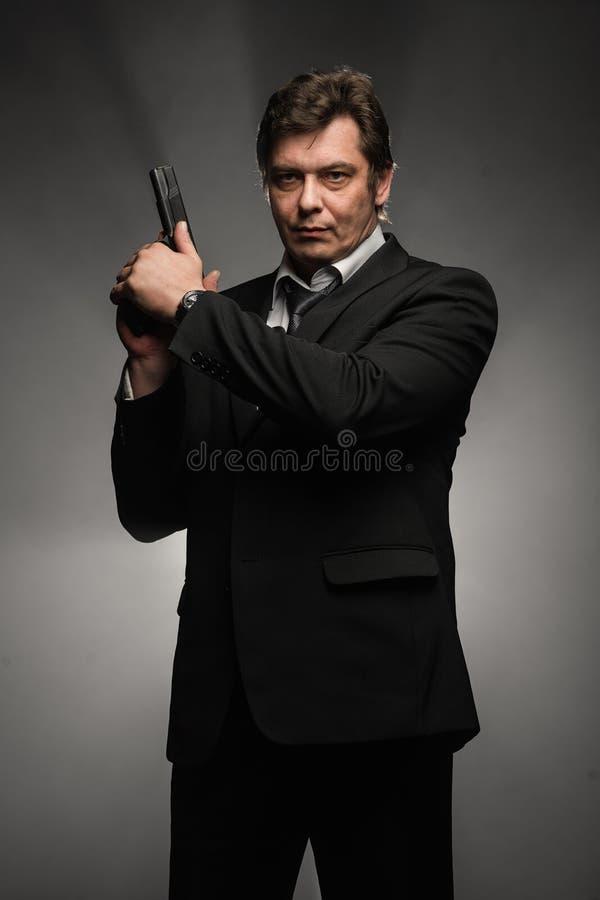 Όμορφο μέσο ηλικίας άτομο ιδιωτικών αστυνομικών με το πυροβόλο όπλο στο σκοτεινό υπόβαθρο στοκ εικόνες
