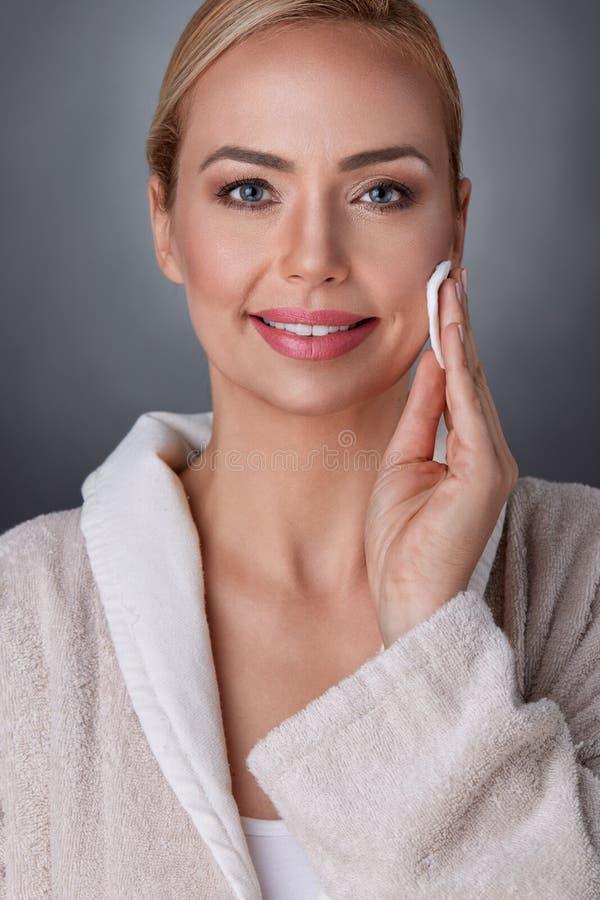 Όμορφο μέσο ηλικίας καθαρίζοντας δέρμα γυναικών στοκ φωτογραφία με δικαίωμα ελεύθερης χρήσης