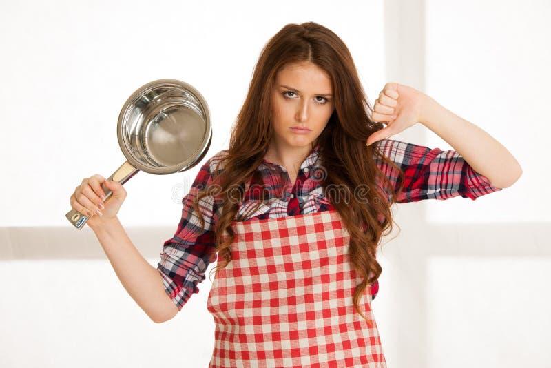Όμορφο μίσος γυναικών που μαγειρεύει παρουσιάζοντας αντίχειρα κάτω στοκ φωτογραφία με δικαίωμα ελεύθερης χρήσης