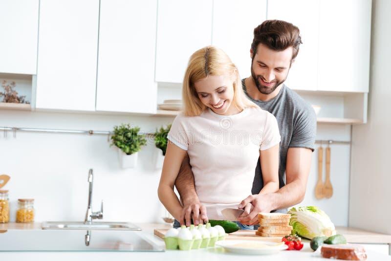 Όμορφο μαγείρεμα ζευγών χαμόγελου μαζί σε μια σύγχρονη κουζίνα στοκ εικόνες