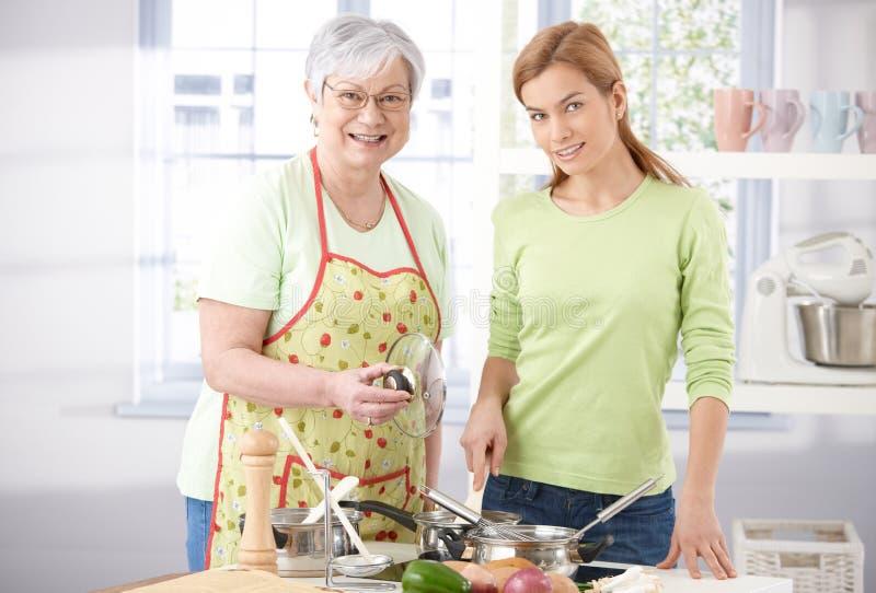 Όμορφο μαγείρεμα κοριτσιών με το ανώτερο χαμόγελο μητέρων στοκ εικόνα