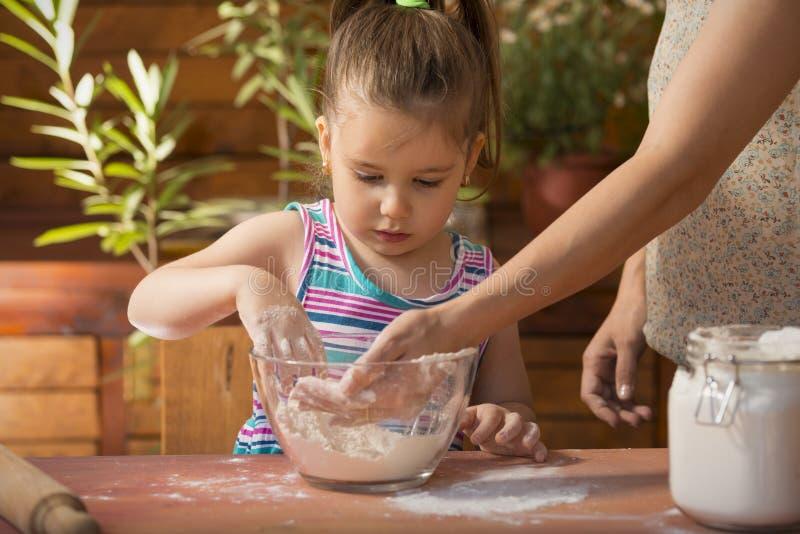 Όμορφο μαγείρεμα μικρών κοριτσιών με τη μητέρα της στοκ εικόνες