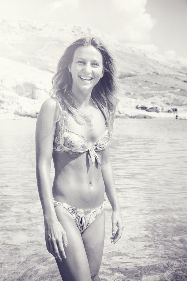 Όμορφο μαυρισμένο κορίτσι σε ένα μπικίνι που στέκεται σε ένα νερό στοκ φωτογραφία