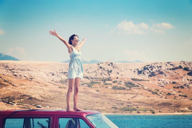 Όμορφο μαυρισμένο κορίτσι σε ένα μπλε φόρεμα που στέκεται σε μια στέγη των κόκκινων όπλων φορτηγών και διάδοσης στοκ εικόνα με δικαίωμα ελεύθερης χρήσης
