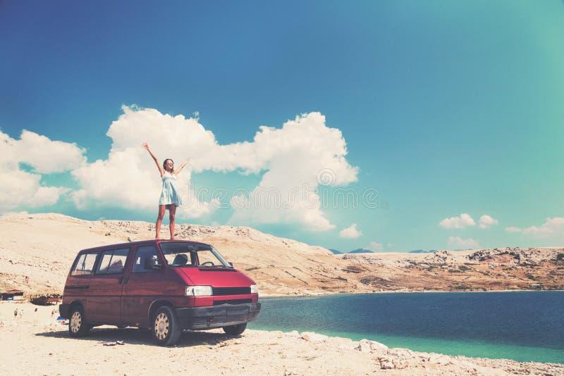 Όμορφο μαυρισμένο κορίτσι σε ένα μπλε φόρεμα που στέκεται σε μια στέγη των κόκκινων όπλων φορτηγών και διάδοσης στοκ φωτογραφίες