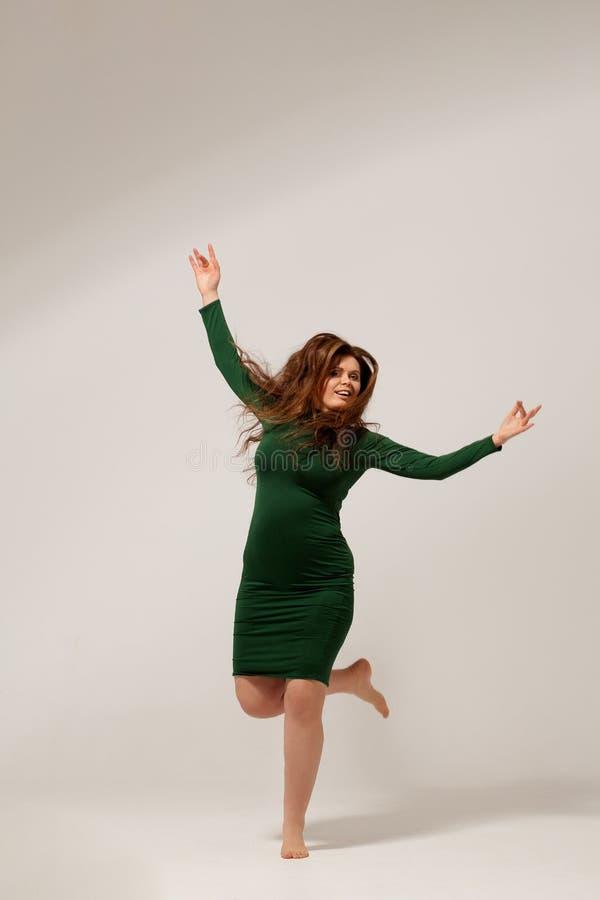 Όμορφο μεγάλο κορίτσι που απομονώνεται στο πράσινο φόρεμα στοκ εικόνες