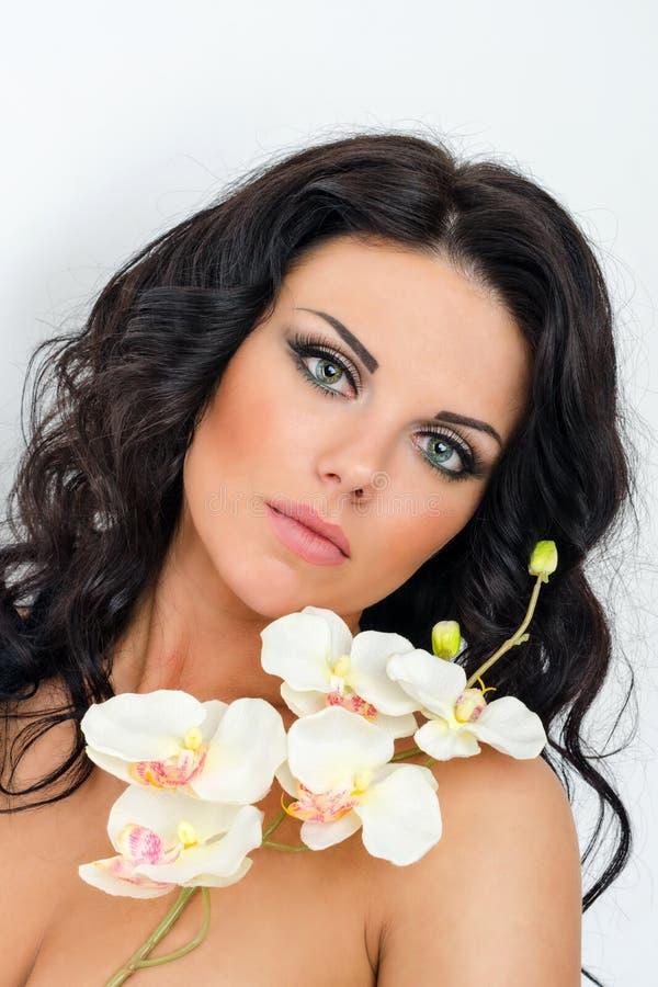 Όμορφο μελαχροινό μαλλιαρό κορίτσι με τις ορχιδέες στο άσπρο υπόβαθρο στοκ εικόνες με δικαίωμα ελεύθερης χρήσης