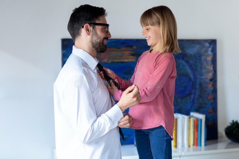 Όμορφο μικρό κορίτσι καθορίζοντας δεσμός του μπαμπά της πρίν πηγαίνει να εργαστεί στο σπίτι στοκ εικόνα