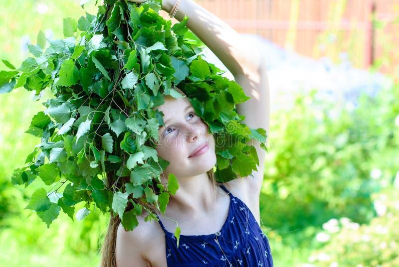 Όμορφο μικρό κορίτσι με ένα στεφάνι των πράσινων φύλλων στοκ εικόνες