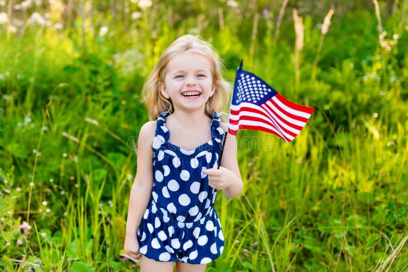 Όμορφο μικρό κορίτσι με τα μακριά σγουρά ξανθά μαλλιά με τη αμερικανική σημαία στοκ εικόνες