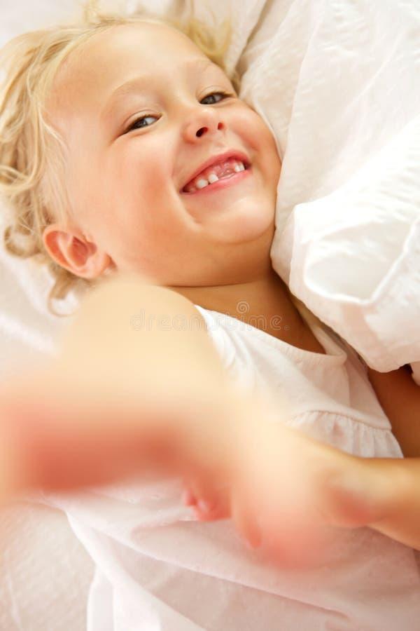 Όμορφο μικρό κορίτσι που βρίσκεται στο κρεβάτι και το χαμόγελο στοκ εικόνα με δικαίωμα ελεύθερης χρήσης