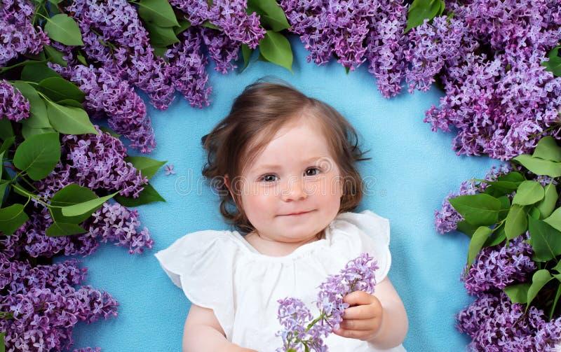 Όμορφο μικρό κορίτσι που βρίσκεται στο μπλε υπόβαθρο με τα ιώδη λουλούδια στοκ εικόνες