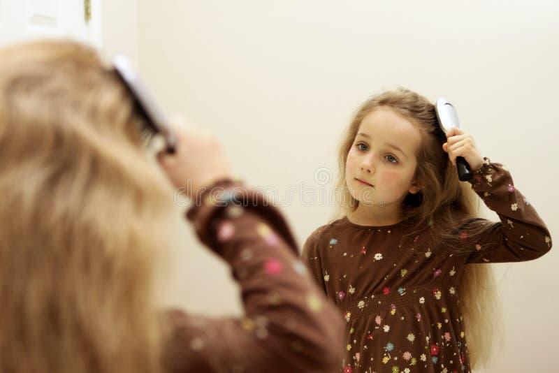 Χαριτωμένη τρίχα βουρτσίσματος μικρών κοριτσιών κοιτάζοντας στον καθρέφτη στοκ φωτογραφίες