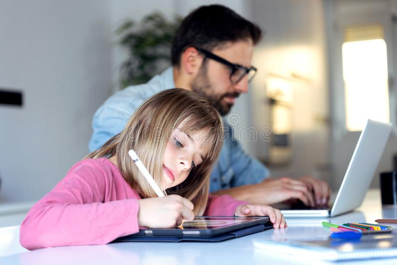 Όμορφο μικρό κορίτσι που επισύρει την προσοχή στην ψηφιακή ταμπλέτα της ενώ ο πατέρας της που εργάζεται με το lap-top στο σπίτι στοκ φωτογραφίες με δικαίωμα ελεύθερης χρήσης