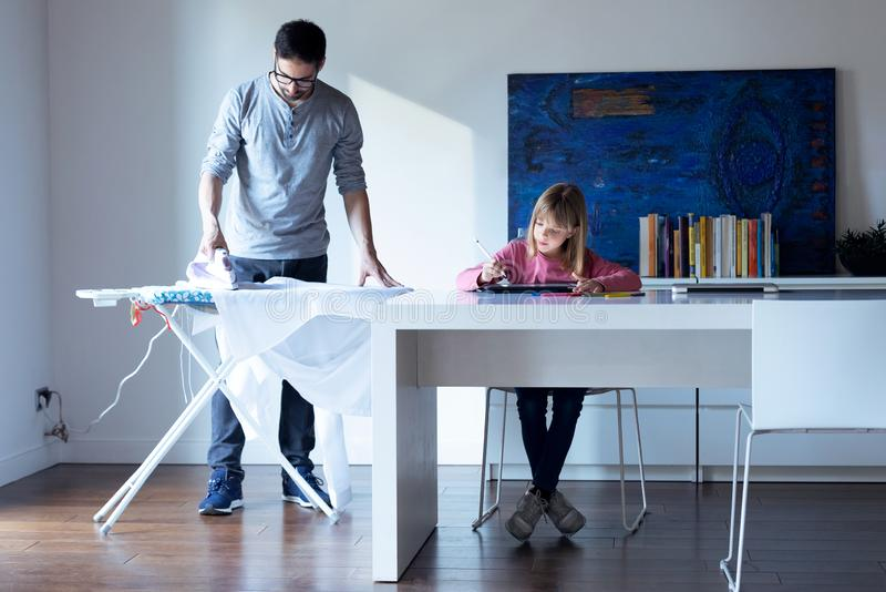 Όμορφο μικρό κορίτσι που επισύρει την προσοχή στο σημειωματάριο ενώ ο πατέρας της που σιδερώνει ένα πουκάμισο στο σπίτι στοκ εικόνα με δικαίωμα ελεύθερης χρήσης
