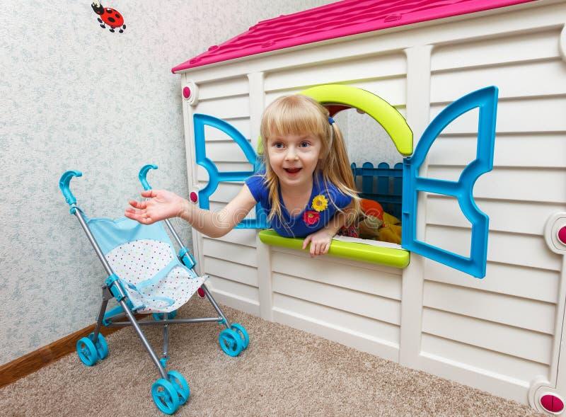 Όμορφο μικρό κορίτσι που κοιτάζει έξω από το σπίτι παιχνιδιών στη φύλαξη στοκ φωτογραφία