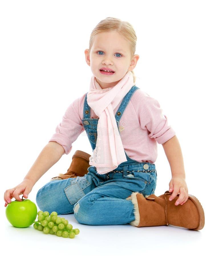 Όμορφο μικρό κορίτσι που κρατά ένα πράσινο μήλο στοκ φωτογραφίες