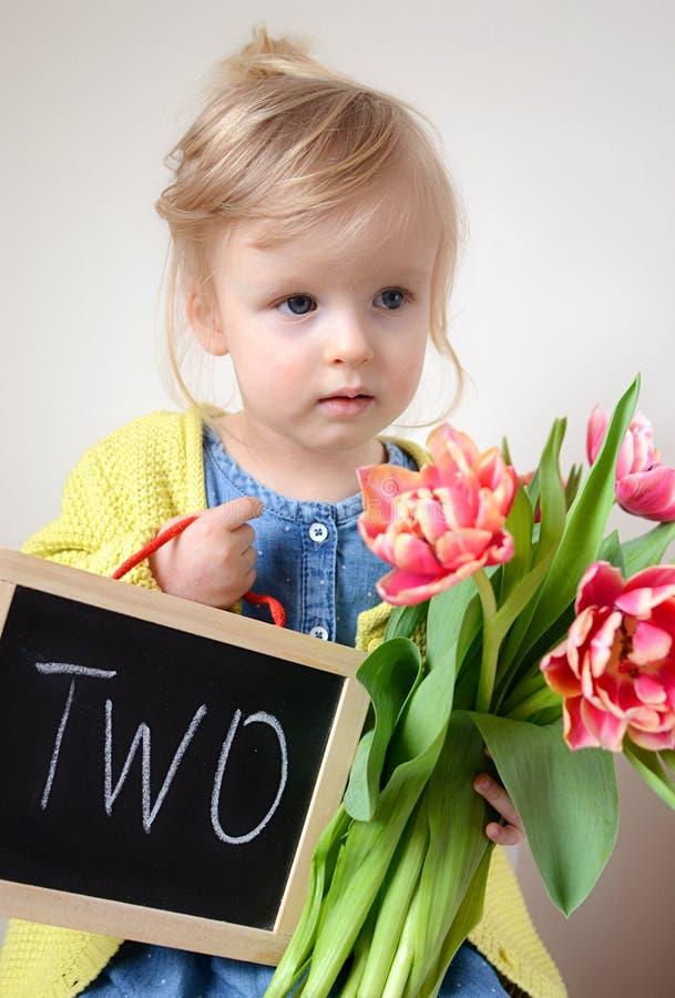 Όμορφο μικρό κορίτσι που κρατά μια ανθοδέσμη των κόκκινων τουλιπών στοκ φωτογραφία
