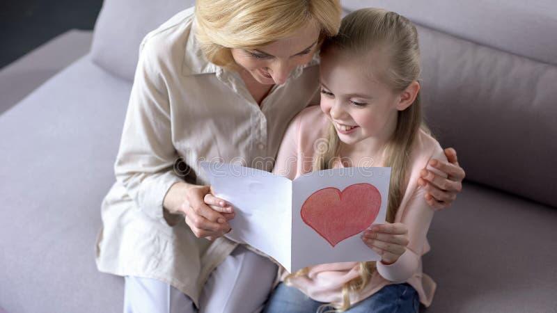 Όμορφο μικρό κορίτσι που παρουσιάζει κάρτα βαλεντίνων της στη γιαγιά, αγάπη παιδιών στοκ εικόνες