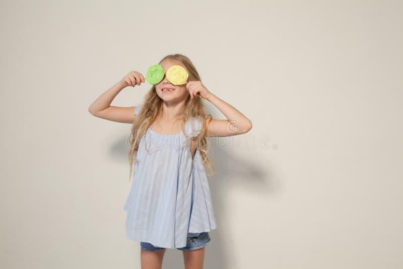 Όμορφο μικρό κορίτσι που τρώει το γλυκό κέικ καραμελών lollipop στοκ φωτογραφία