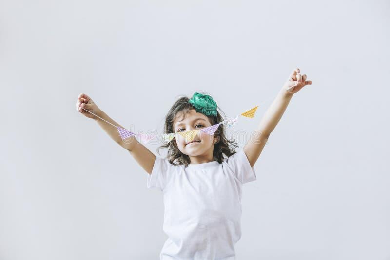 Όμορφο μικρό κορίτσι στο άσπρο υπόβαθρο με τις εορταστικές σημαίες στοκ εικόνες με δικαίωμα ελεύθερης χρήσης