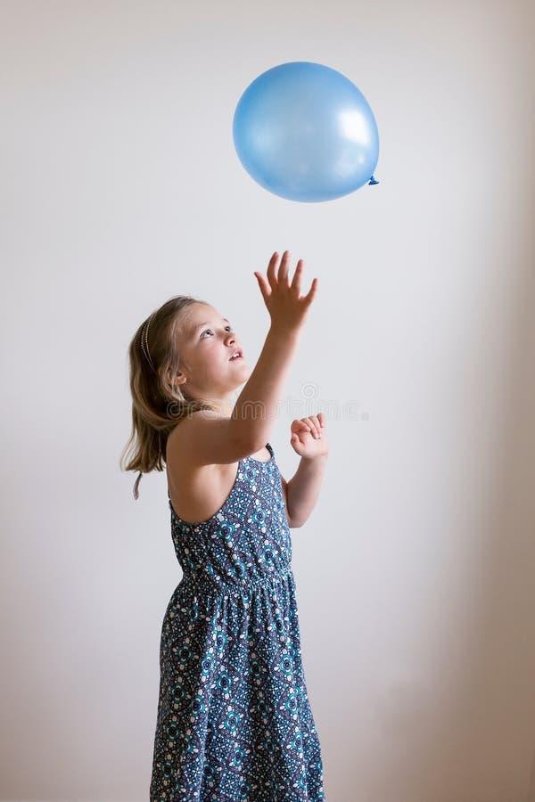 Όμορφο μικρό κορίτσι στο θερινό φόρεμα που ρίχνει το μπαλόνι στοκ φωτογραφία με δικαίωμα ελεύθερης χρήσης