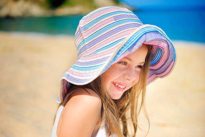 Όμορφο μικρό κορίτσι στο καπέλο φορεμάτων και παραλιών στοκ εικόνα