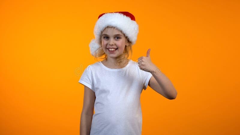 Όμορφο μικρό κορίτσι στο καπέλο santa που παρουσιάζει αντίχειρας-μας και που χαμογελά στη κάμερα, πωλήσεις στοκ φωτογραφίες με δικαίωμα ελεύθερης χρήσης