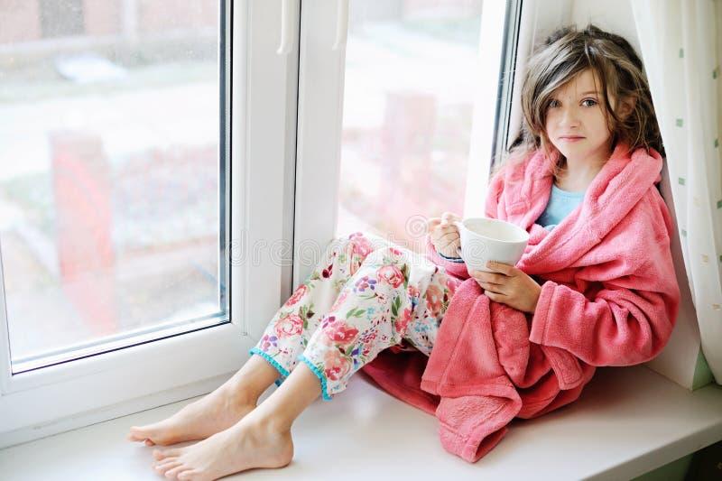 Όμορφο μικρό κορίτσι στο μπουρνούζι με το φλυτζάνι του τσαγιού στοκ εικόνα